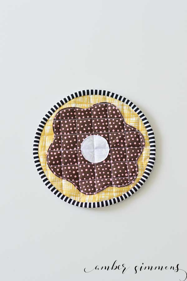 Could your kitchen use more donuts? Follow this tutorial to make a Frosted Donut Hot Pad. Use the Cricut Maker to cut out the pattern to make this adorable pastry pot holder. | ambersimmons.com