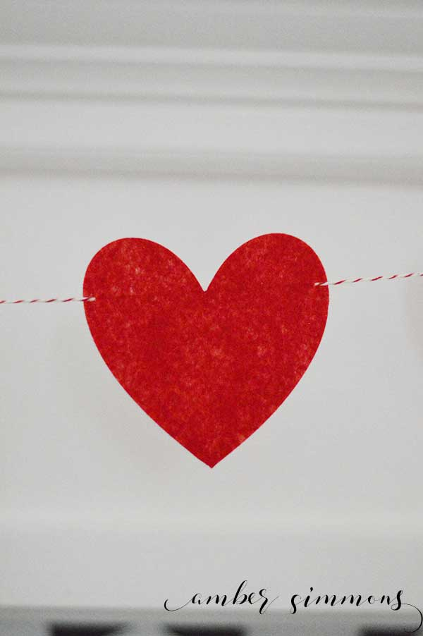 This simple no-sew felt heart garland can be made in just a few minutes, making this quick craft perfect for craft day, girls night, or a last-minute decoration. | ambersimmons.com | #valentine #valentinesday #valentinedecor